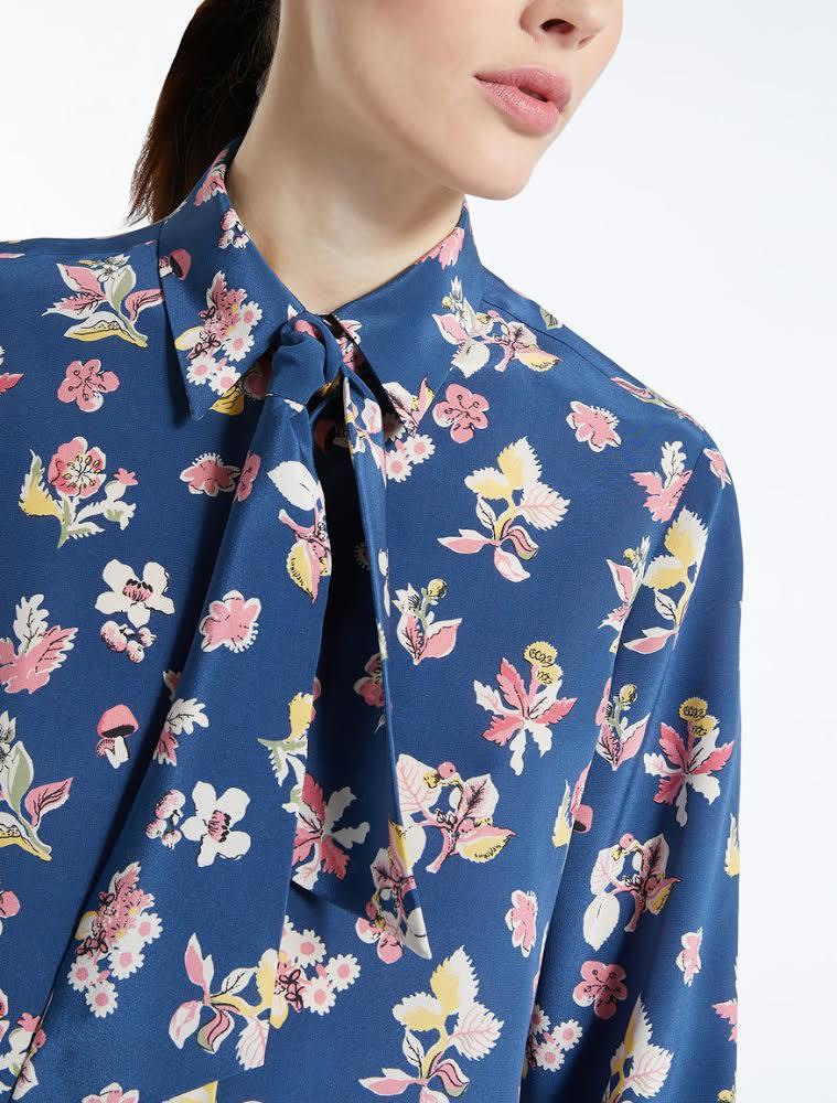 FOTO #10: Modelo con blusa floral de fondo azul.